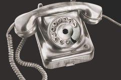 Um telefone de prata antigo do disco do seletor no processamento futurista no fundo preto isolado imagem de stock