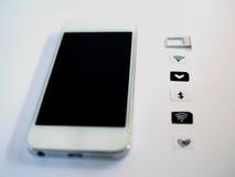 Um telefone esperto branco, uma bandeja de cartão do sim e um papel pequeno simulados como Foto de Stock