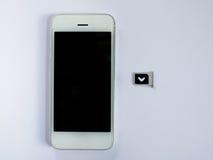 Um telefone esperto branco, uma bandeja de cartão do sim e um papel pequeno simulados como Imagens de Stock