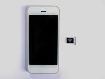 Um telefone esperto branco, uma bandeja de cartão do sim e um papel pequeno simulados como Imagem de Stock