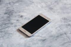 Um telefone esperto com a tela no fundo de pedra cinzento foto de stock royalty free