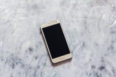 Um telefone esperto com a tela no fundo de pedra cinzento foto de stock