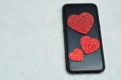 Um telefone esperto indicado com três corações vermelhos do brilho Imagens de Stock Royalty Free