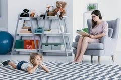 Um terapeuta profissional que faz um diagnóstico de uma criança retraída que se esteja encontrando no assoalho em um escritório d fotografia de stock