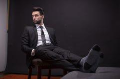 Um terno de relaxamento de assento das peúgas da cadeira do homem novo Fotos de Stock Royalty Free