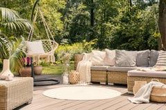 Um terraço grande com um sofá confortável com coxins, um t do lazer foto de stock