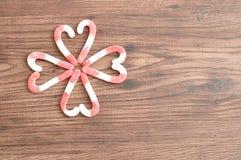 Um teste padrão de flor feito fora dos bastões de doces embalou em formas do coração Fotografia de Stock