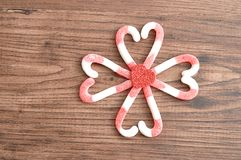 Um teste padrão de flor feito fora dos bastões de doces embalou em formas do coração com um coração vermelho pequeno Foto de Stock Royalty Free