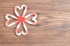 Um teste padrão de flor feito fora dos bastões de doces embalou em formas do coração com um coração vermelho pequeno Imagens de Stock Royalty Free