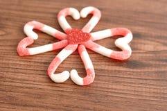Um teste padrão de flor feito fora dos bastões de doces embalou em formas do coração com um coração vermelho pequeno Fotos de Stock