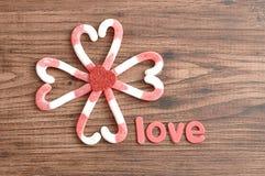 Um teste padrão de flor feito fora dos bastões de doces embalou em formas do coração com um coração vermelho pequeno e o amor da  Imagens de Stock Royalty Free