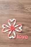 Um teste padrão de flor feito fora dos bastões de doces embalou em formas do coração com um coração vermelho pequeno e o amor da  Imagem de Stock Royalty Free