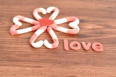 Um teste padrão de flor feito fora dos bastões de doces embalou em formas do coração com um coração vermelho pequeno e o amor da  Imagens de Stock