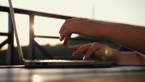 Um texto de datilografia da mulher em um portátil em seu local de trabalho Menina no por do sol no sol Compra em linha eletrônica video estoque