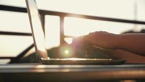 Um texto de datilografia da mulher em um portátil em seu local de trabalho Menina no por do sol no sol Compra em linha eletrônica filme