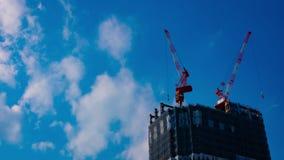 Um timelapse dos guindastes na construção inferior atrás do céu azul no Tóquio filme