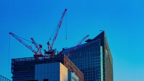 Um timelapse dos guindastes na construção inferior atrás do céu azul no Tóquio video estoque