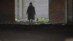 Um tipo duro atravessa a sala empoeirada de uma fábrica abandonada Tiro cinemático mesmo video estoque