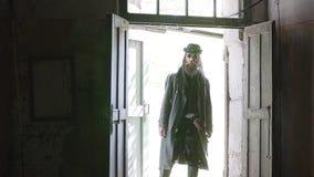 Um tipo duro em uma capa de chuva preta abre a porta a uma sala abandonada com um pontapé video estoque
