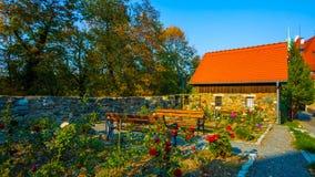 Um tiro bonito de uma casa velha no Polônia //na mola com flores/cadeira vermelhas 2018 do assento fotografia de stock
