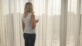Um tiro da janela grande coberta com o tule Um louro grávido com um vidro da água vem à janela e aos começos video estoque