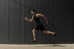 Um tiro da vista lateral de um ajuste novo, do homem atlético que salta e que corre foto de stock royalty free