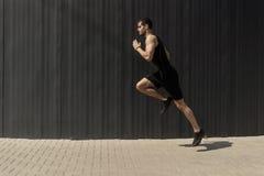 Um tiro da vista lateral de um ajuste novo, do homem atlético que salta e que corre imagem de stock
