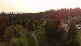Um tiro de filtra??o a?reo de um campo de golfe aninhado em uma floresta sempre-verde com os jogadores de golfe que jogam nos fai vídeos de arquivo