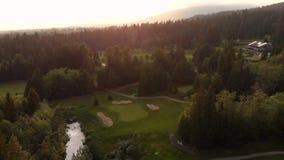 Um tiro de filtra??o a?reo de um campo de golfe aninhado em uma floresta sempre-verde com os jogadores de golfe que jogam nos fai video estoque