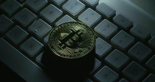 Um tiro de giro de um bitcoin do casascius em um teclado de computador branco filme