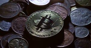 Um tiro de giro de um bitcoin do casascius em uma pilha de moedas internacionais video estoque