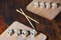 Um tiro detalhado de um grupo de rolos de sushi japoneses e de um dispositivo para seus hashis do uso, que são ficados situados e imagens de stock