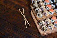 Um tiro detalhado de um grupo de rolos de sushi japoneses e de um dispositivo para seus hashis do uso, que são ficados situados e imagem de stock royalty free