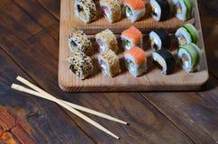 Um tiro detalhado de um grupo de rolos de sushi japoneses e de um dispositivo para seus hashis do uso, que são ficados situados e foto de stock royalty free