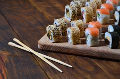 Um tiro detalhado de um grupo de rolos de sushi japoneses e de um dispositivo para seus hashis do uso, que são ficados situados e fotografia de stock