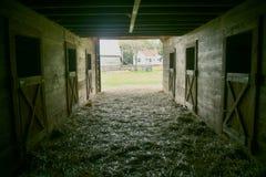 Um tiro do interior de um celeiro velho que olha para fora imagem de stock