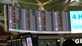 Um tiro handheld do ângulo largo de uma placa da partida em um aeroporto vídeos de arquivo
