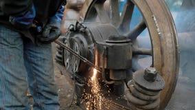 Um tiro próximo às mãos de um homem nas luvas de borracha, que eliminasse a parte do fogo da roda do metal de um bonde ou video estoque