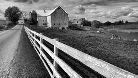 Um tiro preto e branco de um celeiro tradicional de Amish e uma cerca de piquete branca no meio de Ohio, EUA fotografia de stock royalty free