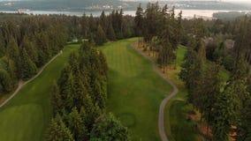 Um tiro a?reo que olha abaixo de um fairway do campo de golfe aninhado em uma floresta com uma vista da entrada de Burrard no fun video estoque