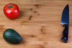 Um tomate e um abacate em uma placa de corte com a faca de um cozinheiro chefe fotografia de stock royalty free