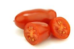 Um tomate italiano inteiro e duas metades Imagem de Stock