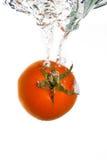 Um tomate que cai na água Fotos de Stock