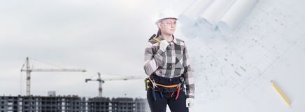 Um trabalhador da construção fêmea no capacete de segurança guarda um martelo fotos de stock