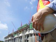 Um trabalhador da construção que guarda um capacete Fotos de Stock Royalty Free