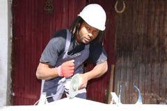Um trabalhador da construção que usa uma máquina do corte de energia fotos de stock royalty free