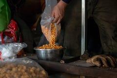 Um trabalhador derrama grões do milho em uma bacia do metal para carregar em um potenciômetro de fritura especial Parte do proces fotos de stock royalty free