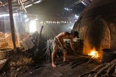 Um trabalhador do carvão vegetal no trabalho em uma pilha do charcoa de madeira ardente lento Fotos de Stock Royalty Free