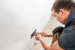 Um trabalhador do eletricista no trabalho da instalação do soquete do cabo de fiação e da tomada do interruptor da luz ou de pare fotografia de stock