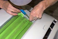 Um trabalhador do reparo do carro durante pastas com uma fita adesiva um p foto de stock royalty free
